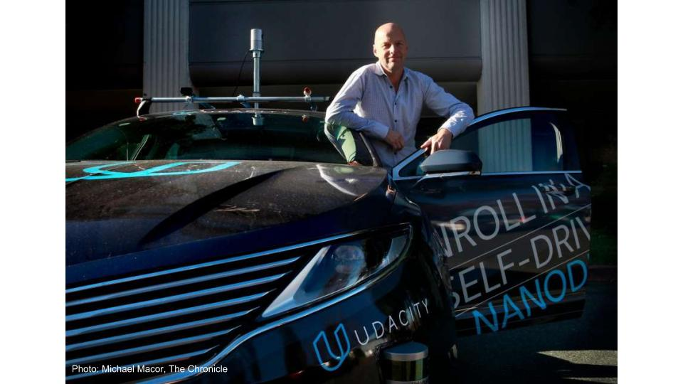 Photo of a Sebastian Thrun with the Udacity driverless car